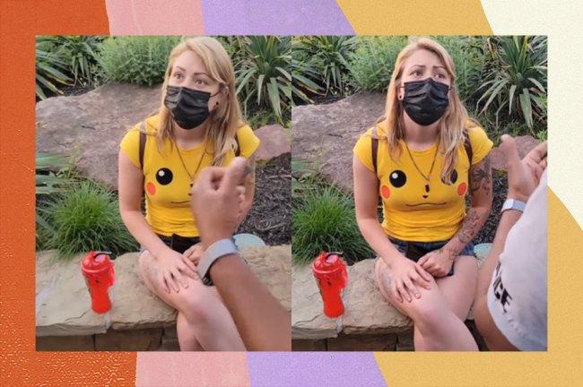 Mulher loira usando máscara de proteção preta, uma camiseta do Pikachu e um short jeans escutando ofensas de um policial. Ela está em um parque.