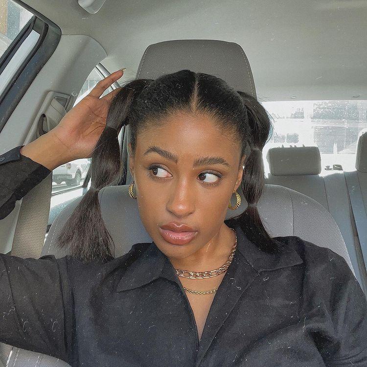 Selfie de uma mulher. Ela está dentro de um carro, veste uma camisa preta, colares de corrente prata e dourado, brinco de argolinha dourado e cabelo preso em um penteado bolha. Ela olha para o lado e segura o cabelo com a mão direita.