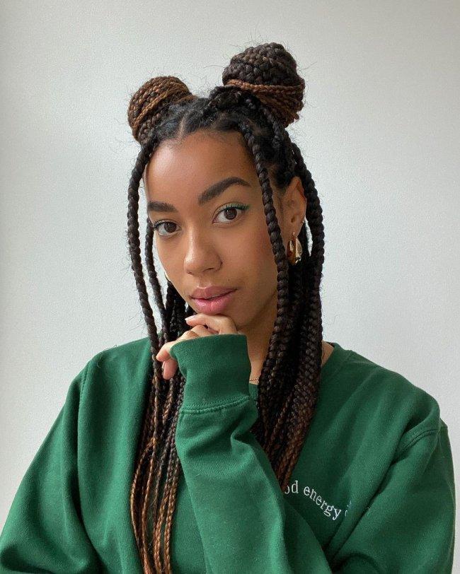 Selfie de uma mulher. Ela veste um moletom verde e cabelo trançado solto com coque dupo. Ela olha para a câmera e apoia a mão esquerda no queixo.