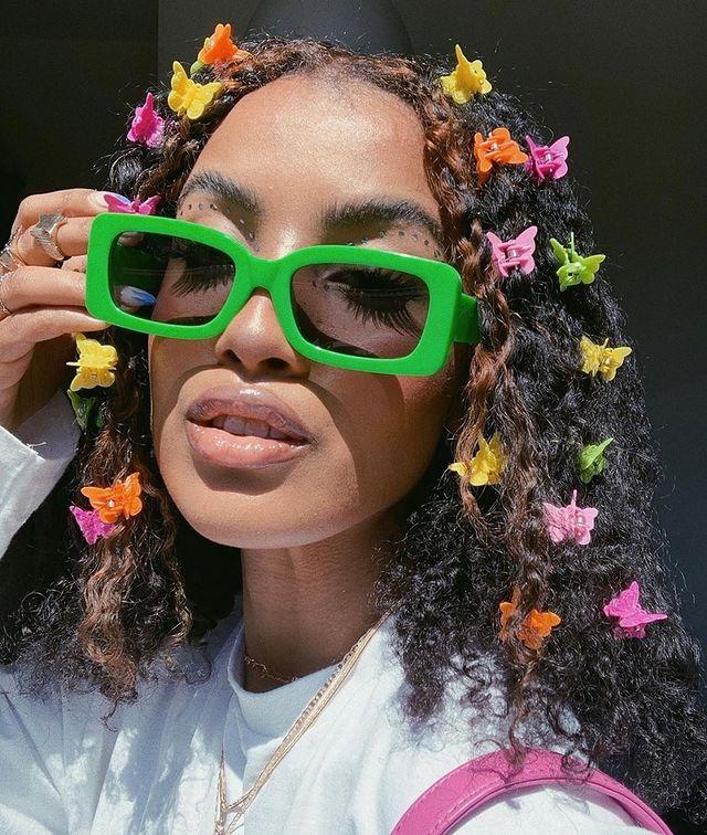 Jovem usando óculos verde com presilha de borboleta colorida no cabelo, com expressão séria.