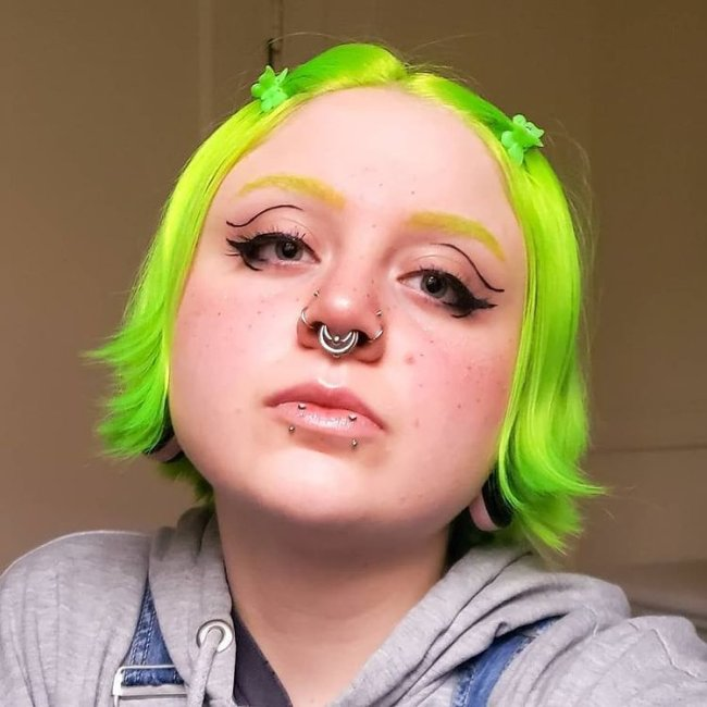 Jovem com expressão séria com cabelo verde, e a cabeça levemente inclinada para cima.
