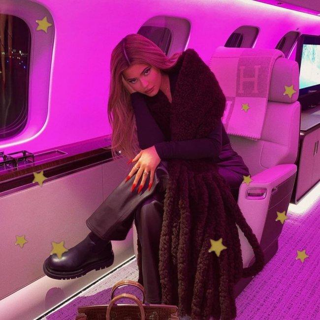 Kylie Jenner posando em avião com bota, uma de suas mãos está apoiando sua cabeça de lado, podemos ver a cadeira do avião e parte da janela.Sua expressão é levemente sorridente.