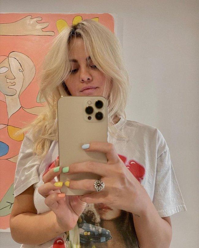 Selfie no espelho da cantora e atriz Selena Gomez. Ela usa uma camiseta branca com estampa vermelha, segura o celular com as duas mãos e está com o cabelo solto. Ela olha para o celular e não sorri para a foto.