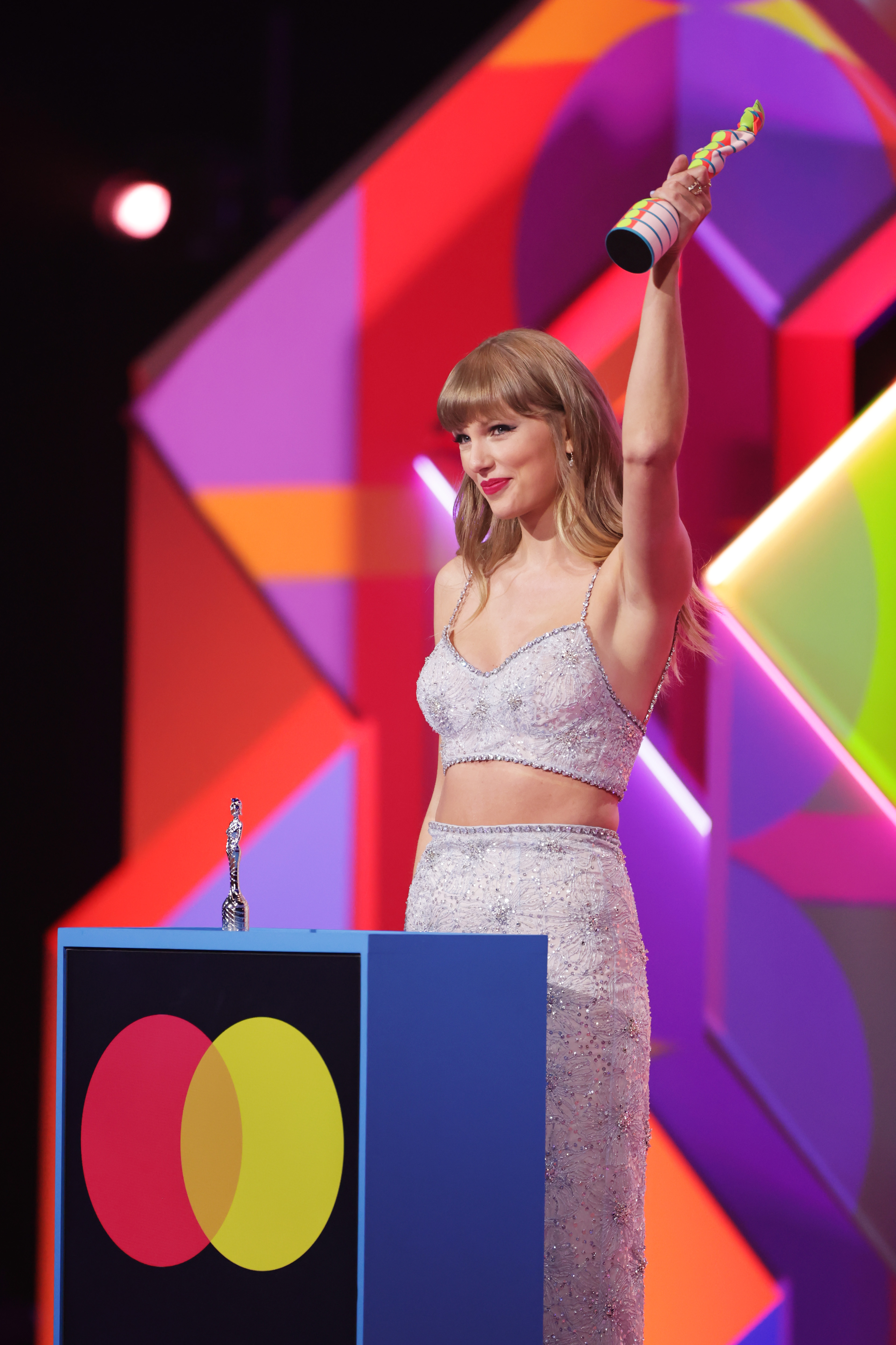 Taylor Swift recebendo prêmio no BRIT Awards 2021. Ela está usando um top cropped e uma saia longa em tom de azul claro com pedrinhas bordas, cabelo solto, segurando a estatueta com uma das mãos para cima. Ela está no palco do evento, sorrindo e comemorando o prêmio.