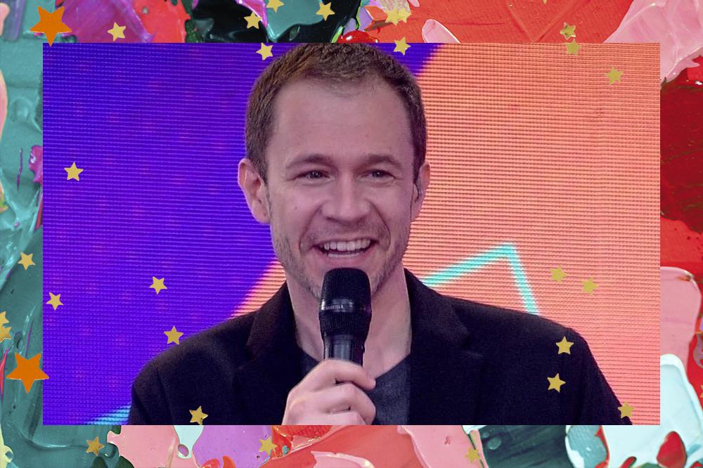 Foto de Tiago Leifert na final do BBB21, ele está sorrindo e segurando um microfone preto com uma das mãos; a imagem tem uma borda de textura de aquarela em tons de vermelho, verde, preto, rosa e roxo; estrelas amarelas e laranjas são usadas como decoração