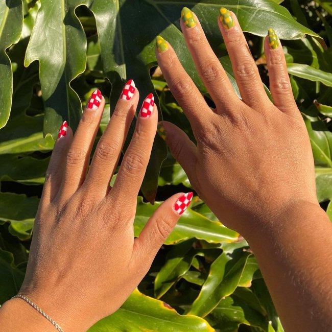 Foto de duas mãos. A mão esquerda está com a unha pintada em uma nail art xadrez branco e vermelho. A mão direita está com a unha pintada em uma nail art xadrez amarelo e verde.