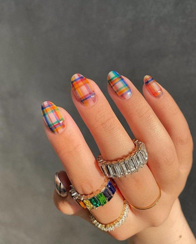 Foto de uma mão com anéis no dedo indicador e médio. A unha está com uma nail art xadrez colorida.