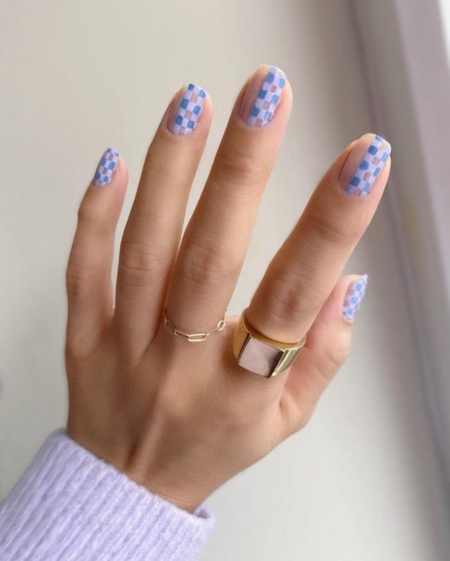 Foto de uma mão com anéis no dedo médio e indicador. A unha está com uma nail art xadrez azul.