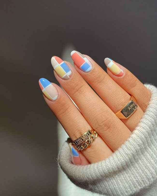 Foto de uma mão com anéis no dedo anelar e indicador. As unhas estão com uma nail art xadrez nas cores azul, amarela, marrom, nude e salmão.