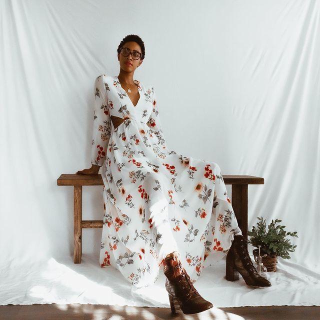 Garota usando vestido longo floral com fundo branco e botinha marrom com salto e bico fino de verniz. Ela está sentada em um banquinho de madeira, com as duas mãos para trás do corpo. Ao fundo, há um pano branco que serve como cenário para a foto.