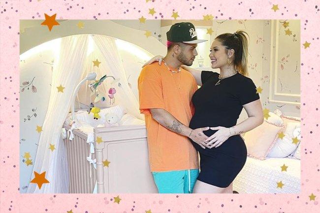 Imagem de Zé Felipe segurando a barriga de Virgínia Fonseca, grávida de Maria Alice. Ela usa um vestido justo preto e ele uma camiseta laranja