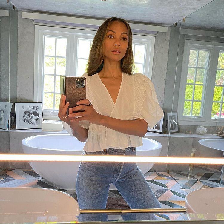 Selfie no espelho de Zoe Saldana; ela está no banheiro usando calça jeans clara e blusa branca; ao fundo é possível ver uma banheira e janelas refletindo a luz do dia; a expressão da atriz é mais séria e a foto está sendo tirada de um celular com capinha escura