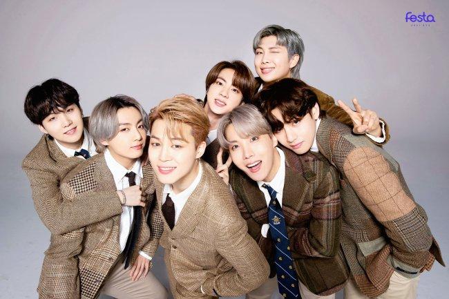 Integrantes do BTS usando roupas em tons de marrom posando para foto em fundo cinza