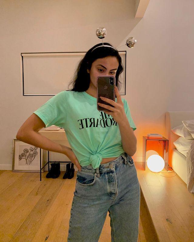 Camila Mendes tirando selfie de frente para o espelho, o celular cobre parte de seu rosto, ela usa tiara com bolinhas e camiseta verde água com nózinho na barriga.