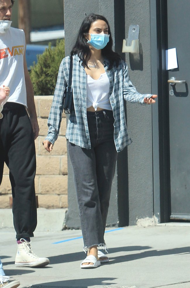 Camila Mendes caminhando pelas ruas de Los Angeles, usando máscara de proteção, camisa xadrez, calça jeans e chinelo branco.
