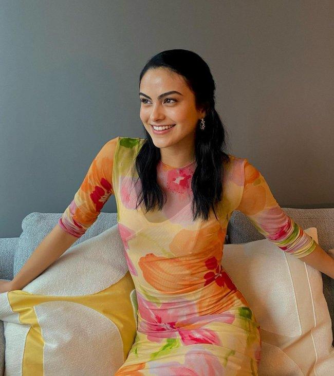 Camila Mendes sentada em sofá branco, com os braços abertos, e expressão sorridente, ela usa vestido semitransparente com estampas nas cores rosa, laranja e verde.