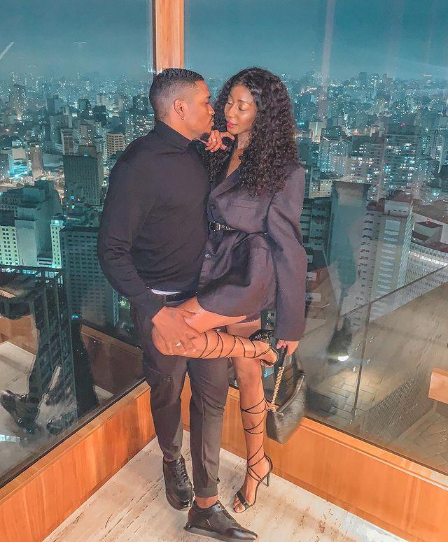 Casal posando em frente a parede de vidro, o rapaz levanta a perna da moça. Os dois estão com uma expressão séria e as roupas que eles vestem são pretas.