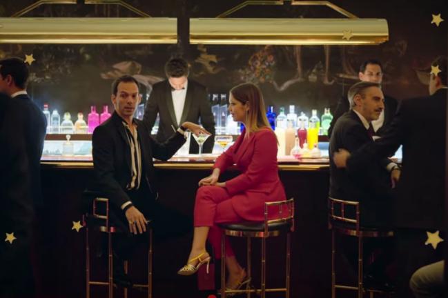 Personagem Cayetana do seriado Elite está sentada de lado, com um homem, ela usa conjunto monocromatico rosa pink e está em um bar.