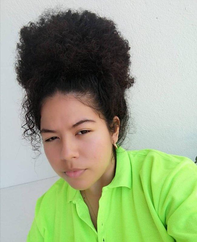 Jovem posando com expressão séria, usando camisa verde em frente a pa