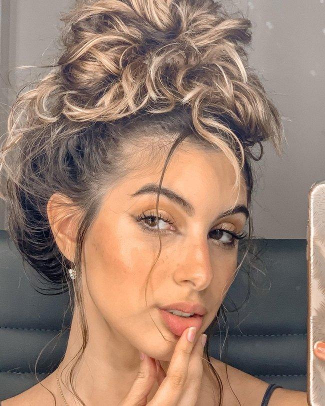 Jovem posando para selfie, só podemos ver seu rosto, ela está com o cabelo preso em um coque bagunçado, sua expressão é séria.