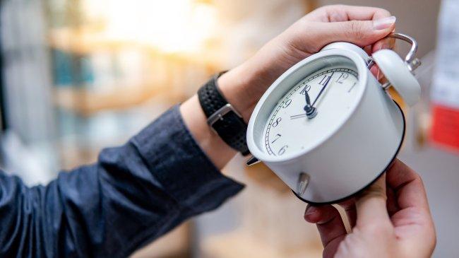 Foto mostrando a mão de uma pessoa ajustando o horário de um relógio