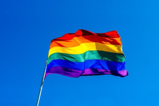 Bandeira LGBTQIA+ hasteada, e ao fundo, céu azul