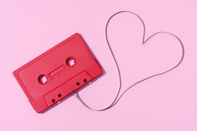 Uma fita cassete vermelha sobre um fundo rosa. A fitinha saindo dela forma um coração.