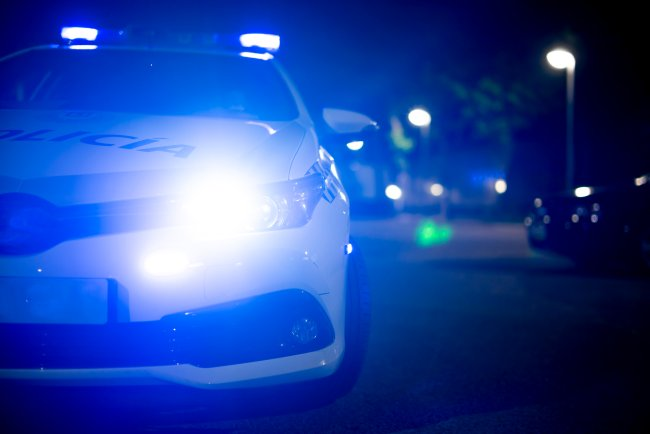 Imagem que mostra uma viatura de polícia com as luzes ligadas em uma rua à noite
