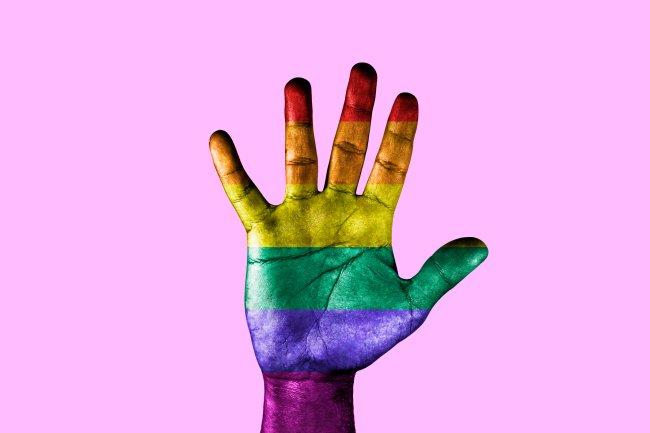 Sobre um fundo rosa, uma mão pintada com as cores da bandeira LGBTQIA+ faz o sinal de pare