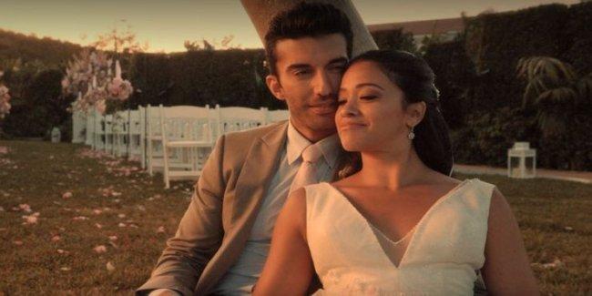Um casal, durante um casamento, abraçados. Ao fundo o local da cerimônia, com as cadeiras e o altar.