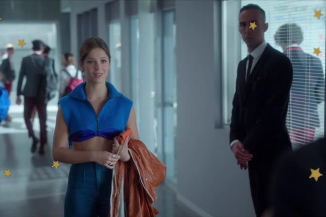 Personagem Cayetana do seriado Elite no corredor da escola carregando sua blusa marrom em uma das mãos.