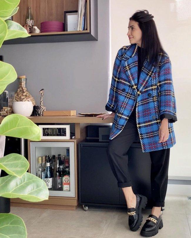 Jovem posando em sua cozinha, olhando para o lado, usando sobretudo xadrez azul com calça preta e mocassim.