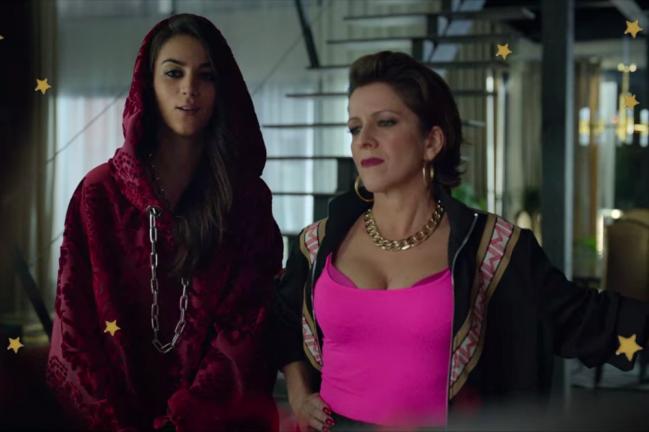 Foto com foco na Rebeca e sua mãe, do seriado Elite, Rebeca usa moletom vermelho e sua mãe blusa rosa pink. Elas estão em suas casas posando em frente a uma escada.