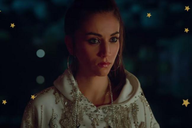 Foco na personagem Rebeca do seriado Elite, com expressão séria usando moletom branco com pedrarias.