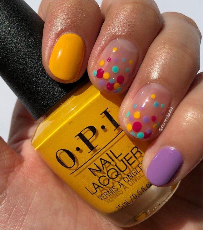 Foto com destaque nas unhas com nail art de bolinha, dessa vez com algumas unhas lilás, outras amarelas, e outras com bolinhas nas cores lilás, vermelho, amarelo e verde.