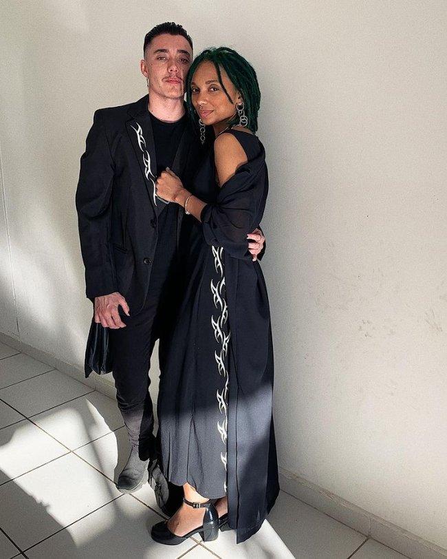 Casal encostado em parede branca abraçado usando roupas pretas. Os dois tem uma expressão séria.