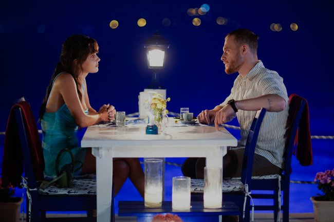 Eda e Serkan jantando; os dois estão sentados um de frente para o outro e se encaram; o céu azul da noite ilustra quase todo o fundo da imagem
