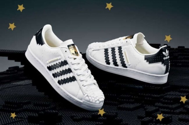 Foto com foco nos novos modelos do tênis branco, com listra preta e posicionados em fundo preto.