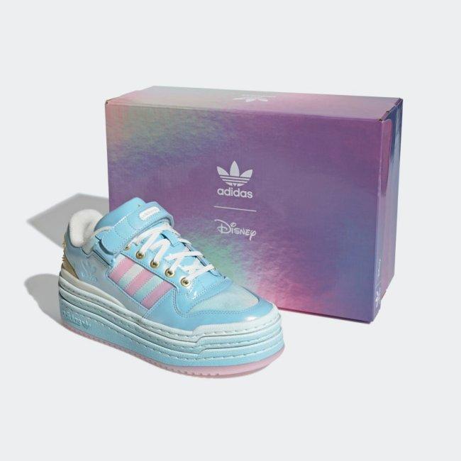 Tênis ao lado da caixa com degradê roxo, azul e rosa. O Tênis é azul com detalhes em rosa e dourado.