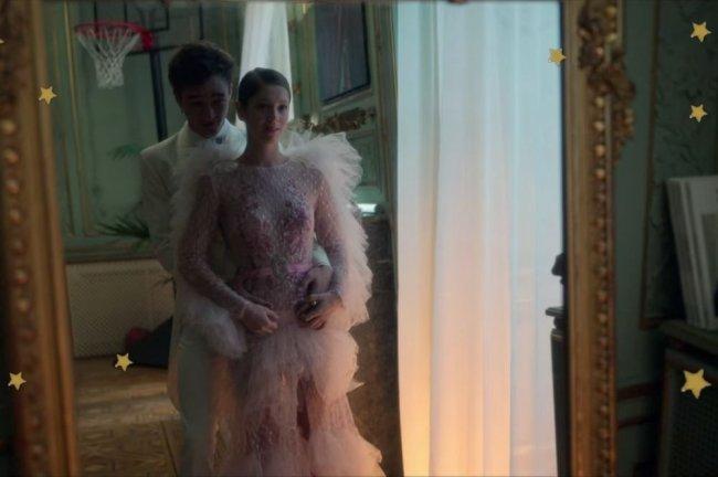 Personagens do seriado Elite, posando frente a espelho, abraçados, com expressão pensativa. Cayetana veste vestido delicado em camadas com detalhes em branco e rosa.