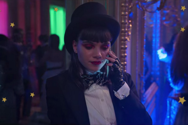 Foto com foco na personagem Mencía usa cartola e smoking com gravata borboleta em Elite.