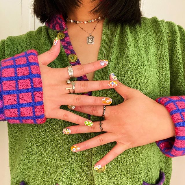 Foto do colo de uma mulher usando diversos anéis e colares com um cardigan verde com manga estampada.