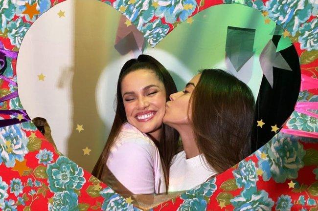 Juliette e Anitta; a cantora está dando um beijo na bochecha de Juliette, que sorri com os olhos fechados; a foto foi postada com uma moldura de coração e a uma textura de flores azuis com fundo vermelho; estrelas amarelas e laranjas decoram a imagem