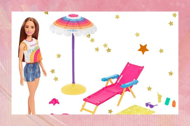 Foto de uma Barbie com roupa de praia ao lado de uma espreguiçadeira, um guarda-sol e outros itens de praia, como baldinho de areia