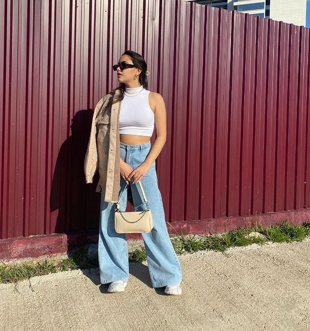 Foto de uma mulher na calçada. Ela usa uma blusa branca de gola alta sem manga, calça wide leg, tênis branco, casaco de veludo bege e bolsa bege. Ela olha para o lado e não sorri.