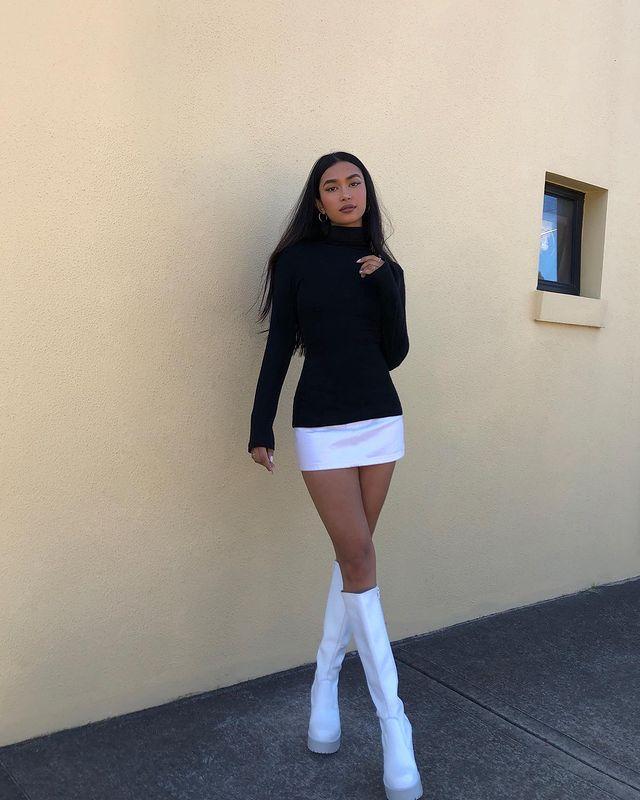 Foto de uma mulher na frente de uma parede rosa. Ela usa uma blusa preta de gola alta e manga longa, saia branca e bota de cano alto branca. Ela olha para a câmera e não sorri.