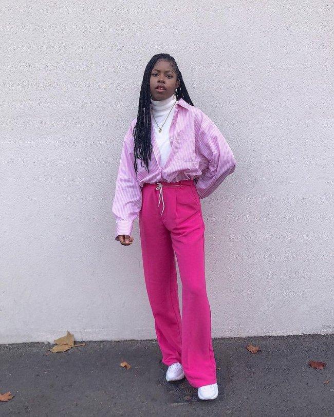 Foto de uma mulher na rua. Ela usa uma blusa de gola alta branca, camisa rosa com listras brancas aberta, calça rosa e tênis branco. Ela olha para a câmera e não sorri.