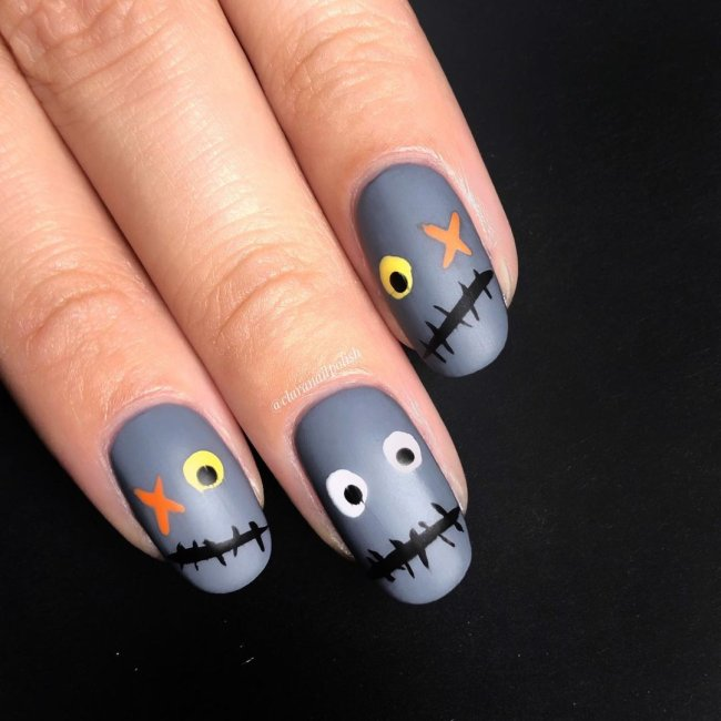 Foto com destaque nas unhas com nail art de bolinha, dessa vez com fundo cinza e formando um monstrinho com olhos de bolinha nas cores cinza, preto, laranja e amarelo.