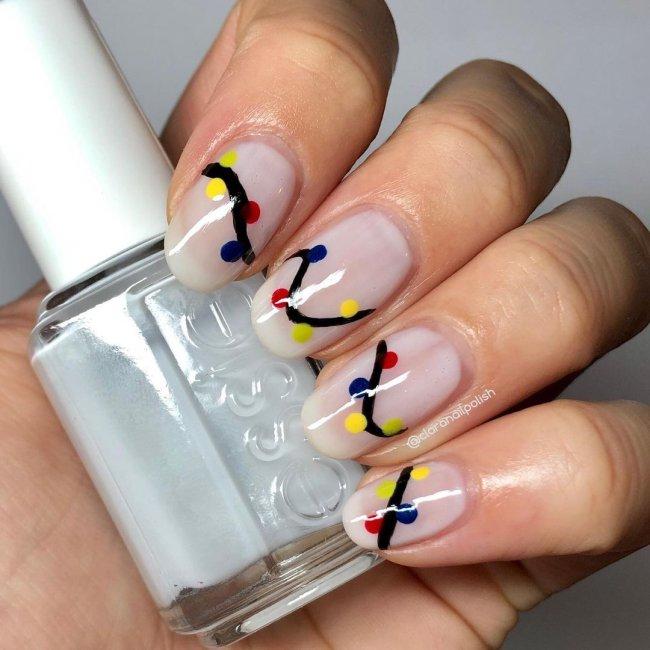 Foto com destaque nas unhas com nail art de bolinha, dessa vez formando o desenho de um pisca-pisca com fundo claro e bolinhas amarela, verde, preto e vermelha.