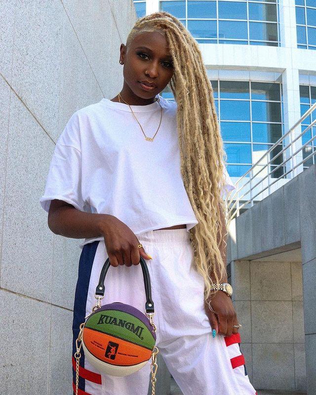 Foto de uma mulher perto das rampas de um edifício. Ela usa uma camiseta branca, calça de moletom rosa clara e segura a bolsa em formato de bola de basquete na mão direita. Ela olha para a câmera e não sorri.